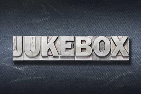 jukebox word made from metallic letterpress on dark jeans background