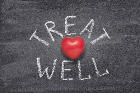 treat well phrase handwritten on chalkboard with red heart symbol instead of O