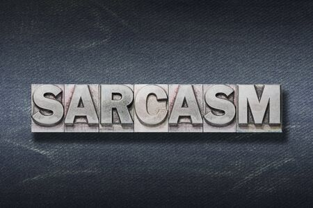 sarcasm word made from metallic letterpress on dark jeans background