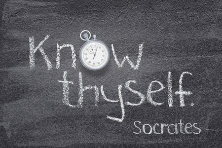 Know thyself - quote of ancient Greek philosopher Socrates written on chalkboard with vintage stopwatch instead of O