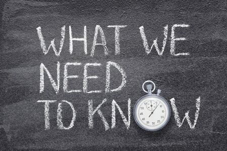 what we need to know phrase written on chalkboard with vintage precise stopwatch Reklamní fotografie