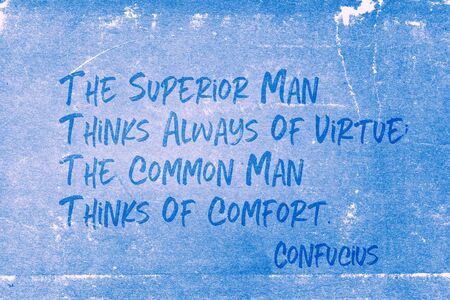 The superior man thinks always of virtue; the common man thinks of comfort - ancient Chinese philosopher Confucius quote printed on grunge blue paper Foto de archivo