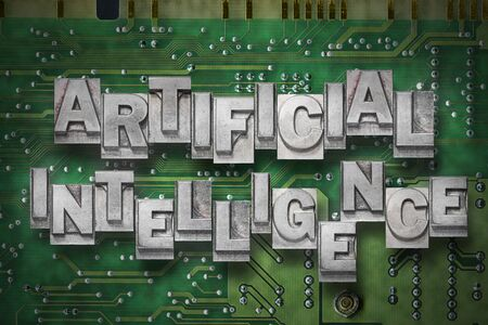 artificial intelligence phrase made from metallic letterpress blocks on the pc board background Stock Photo