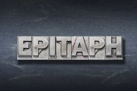epitaph word made from metallic letterpress on dark jeans background