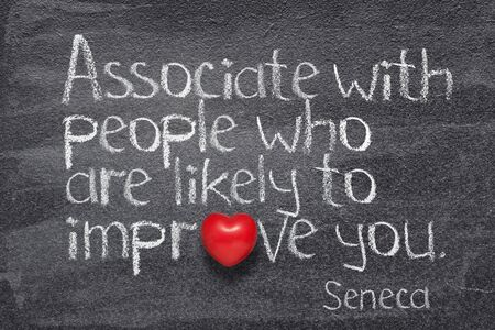 Associate with people who are likely to improve you - quote of ancient Roman philosopher Seneca written on chalkboard  Banco de Imagens
