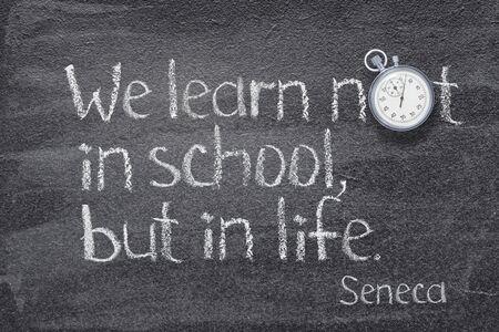 We learn not in the school, but in life - quote of ancient Roman philosopher Seneca written on chalkboard Banco de Imagens