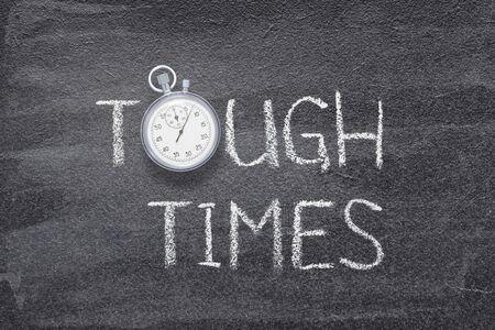 tough times phrase written on chalkboard with vintage precise stopwatch Reklamní fotografie