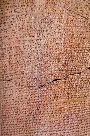 ancient Assyrian clay tablet document covered by cuneiform
