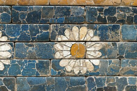 ancient Babylonian glazed brick wall with white flower decoration Stock Photo
