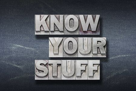 know your stuff phrase made from metallic letterpress on dark jeans background