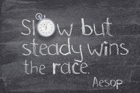 Slow but steady wins the race - quote of ancient Greek story teller Aesop written on chalkboard with stopwatch instead of O
