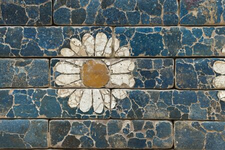damaged brick wall with simple flower image from ancient Babylon