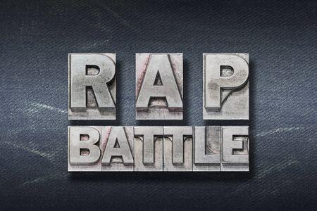 rap battle phrase made from metallic letterpress on dark jeans background Фото со стока