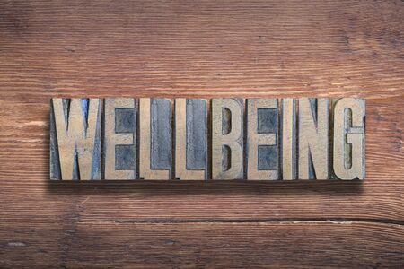 wellbeing word combined on vintage varnished wooden surface Imagens