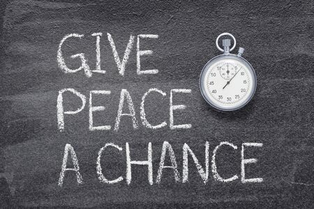 give peace a chance phrase written on chalkboard with vintage precise stopwatch