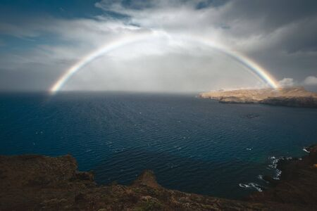 full rainbow above stormy ocean close to Madeira Island, Portugal