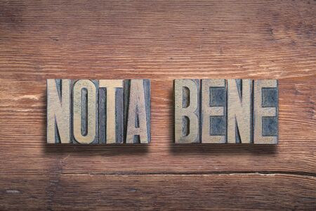 nota bene ancient Latin saying meaning «take note» combined on vintage varnished wooden surface