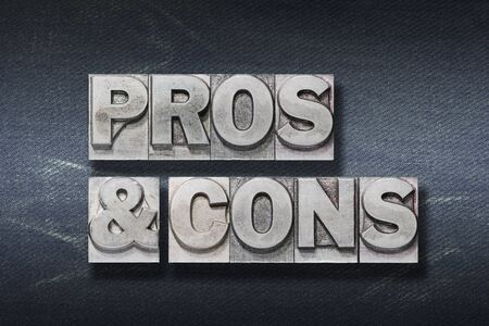 pros & cons phrase made from metallic letterpress on dark jeans background