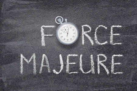 force majeure phrase written on chalkboard with vintage precise stopwatch