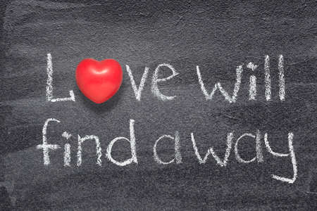 Love will find a way saying written on chalkboard with red heart symbol