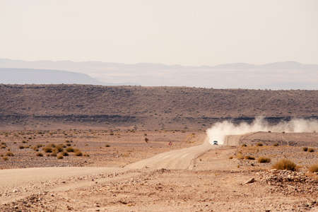 distant car moving by gravel road in desert of Namibia