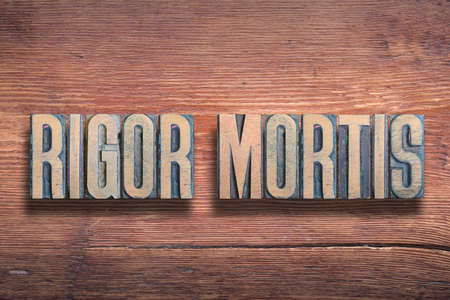 rigor mortis ancient Latin saying meaning - stiffness of death, combined on vintage varnished wooden surface