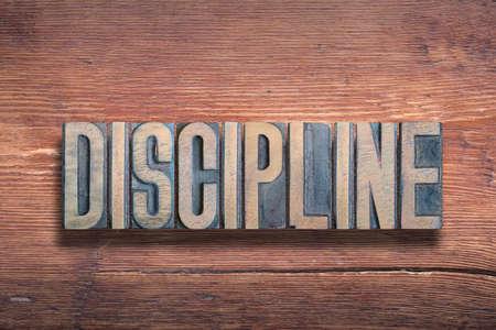 discipline word combined on vintage varnished wooden surface