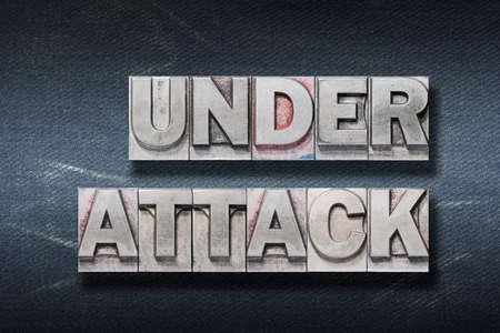 under attack phrase made from metallic letterpress on dark jeans background