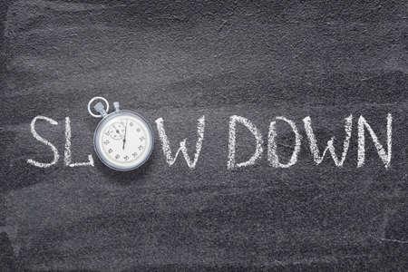 slow down phrase written on chalkboard with vintage precise stopwatch