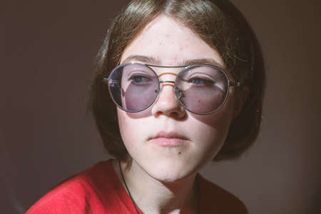 closeup portrait of serious teenage girl in glasses