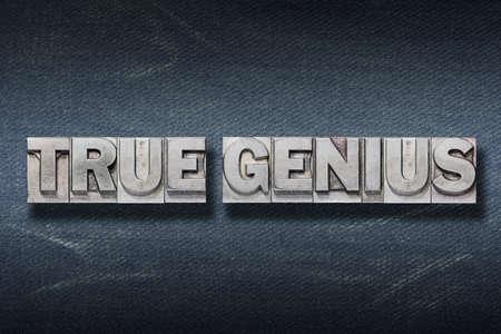 true genius phrase made from metallic letterpress on dark jeans background