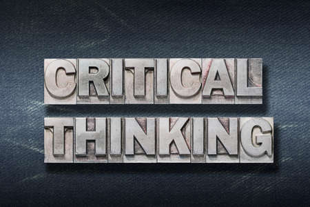 critical thinking phrase made from metallic letterpress on dark jeans background