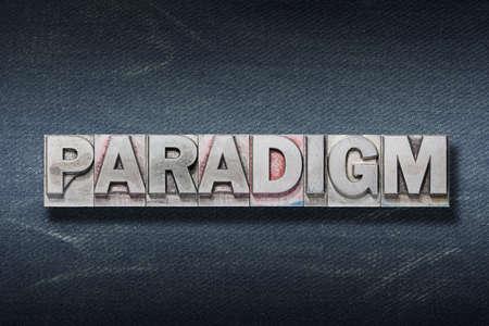 paradigm word made from metallic letterpress on dark jeans background