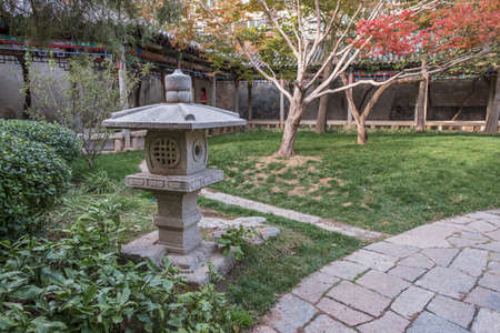 traditional Chinese garden autumn landscape with focus on stone lantern