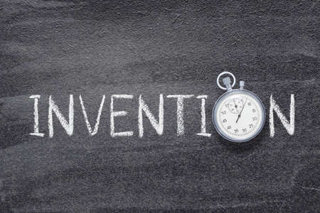 invention word written on chalkboard with vintage precise stopwatch