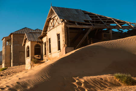 abandoned ruins of Kolmanskop town among sand dunes in desert of Namibia by early morning