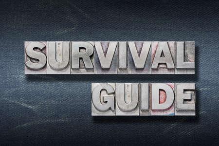 survival guide phrase made from metallic letterpress on dark jeans background Stok Fotoğraf