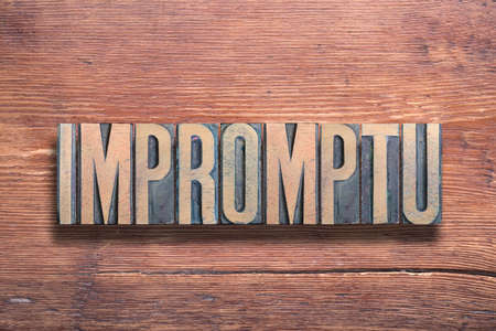 impromptu word ancient Latin word meaning - spontaneous, combined on vintage varnished wooden surface Stok Fotoğraf