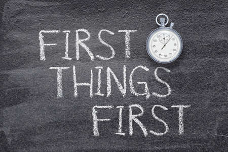 first things first phrase written on chalkboard with vintage precise stopwatch