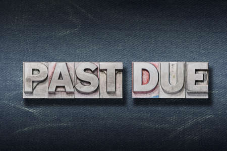past due phrase made from metallic letterpress on dark jeans background