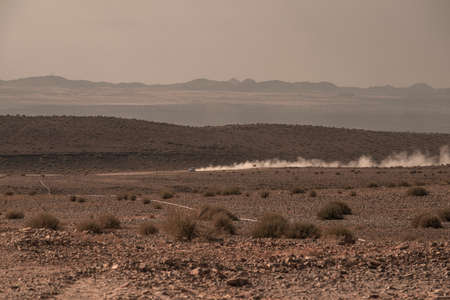 distant car moving by desert gravel road with dust clouds trace in Namibia