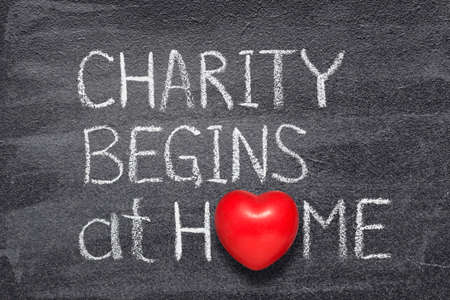 Charity begins at home saying written on chalkboard with red heart symbol Stok Fotoğraf