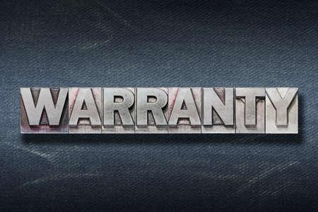 warranty word made from metallic letterpress on dark jeans background