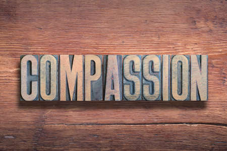 compassion word combined on vintage varnished wooden surface