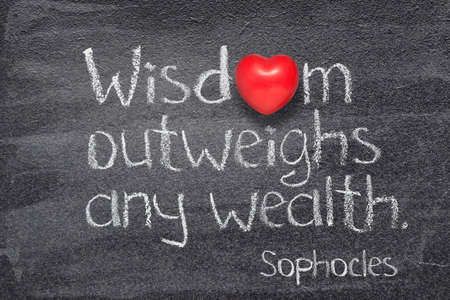 Wisdom outweighs any wealth - quote of ancient Greek philosopher Sophocles written on chalkboard with red heart symbol instead of O