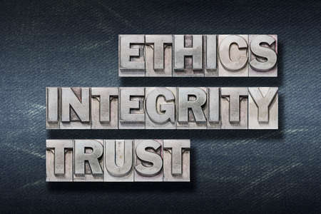 ethics, integrity, trust words made from metallic letterpress on dark jeans background