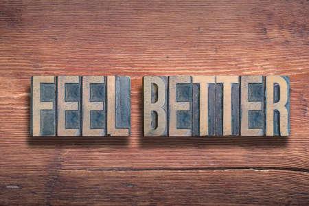 feel better phrase combined on vintage varnished wooden surface Stok Fotoğraf