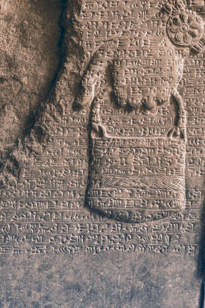 ancient Assyrian cuneiform carved on stone wall over human hand relief Stok Fotoğraf