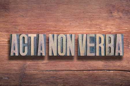 acta non verba ancient Latin saying meaning «deeds, not words» combined on vintage varnished wooden surface