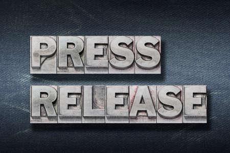 press release phrase made from metallic letterpress on dark jeans background